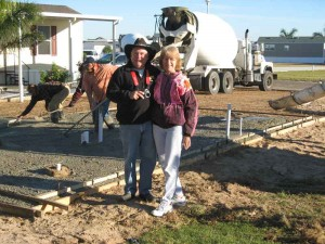 Betty and Jay pose in front of their lot with the cement mixer behind them.