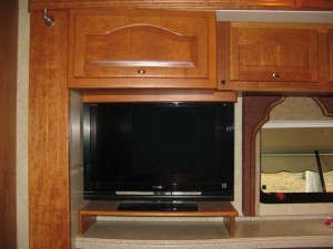 Our new TV sits on a little table and is secured to the cupboard above. The old TV box has a new door that matches the other cupboard doors above the counter.