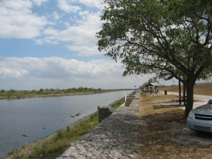 By the lake channel is a one-way street with shaded picnic tables in a park.